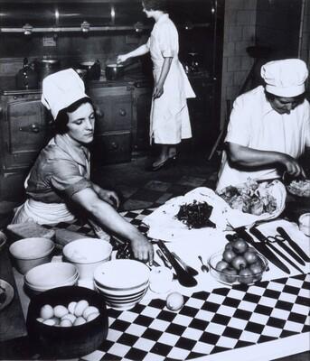 Cook and kitchen maids preparing dinner