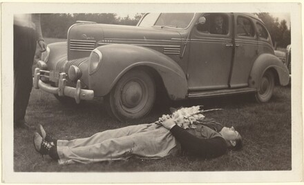 Untitled (Man lying on grass holding flowers in front of car)
