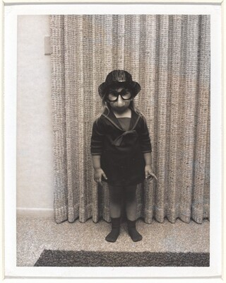Untitled (Girl with fake glasses and nose in front of curtain)