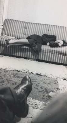 Untitled (Woman sleeping on striped couch with foot in foreground)
