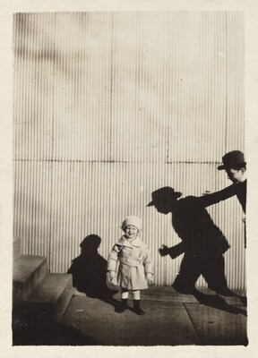 Untitled (Child with shadow of man against corrugated fence)