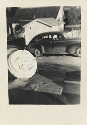 Untitled (Cake held in foreground with car behind)