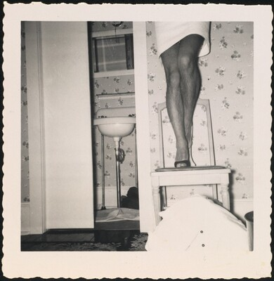 Untitled (Man's legs in skirt on chair)