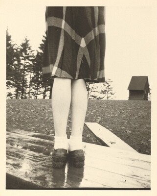 Untitled (Plaid skirt and legs on wood table)