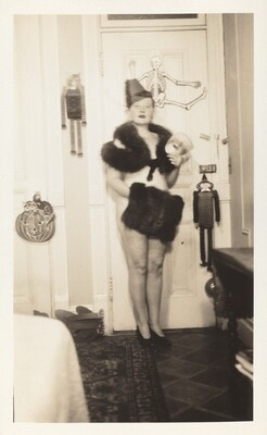 Untitled (Woman posed against door in collar and muff with Halloween decorations