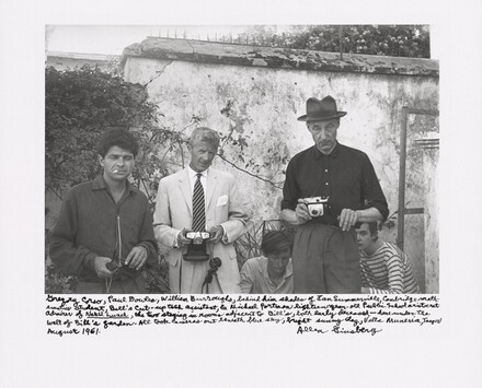 Gregory Corso, Paul Bowles, William Burroughs, behind him shades of Ian Summerville, Cambridge mathematics student, Bill's cut-up tech assistant, and Michael Portman, eighteen-year-old Public School aristocrat admirer of Naked Lunch, the two staying in rooms adjacent to Bill's, both early deceased — here under the wall of Bill's garden. All took cameras out beneath blue sky, bright sunny day, Villa Muneria, Tanger August 1961.