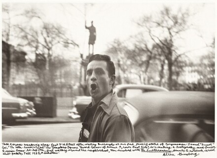 Jack Kerouac wandering along East 7th Street after visiting Burroughs at our pad, passing statue of Congressman Samuel Sunset Cox, The Letter-Carrier's Friend in Tompkins Square toward corner of Avenue A, Lower East Side; he's making a Dostoyevsky mad-face or Russian basso be-bop Om, first walking around the neighborhood, then involved with The Subterraneans, pencils & notebook in wool shirt-pockets, Fall 1953, Manhattan.