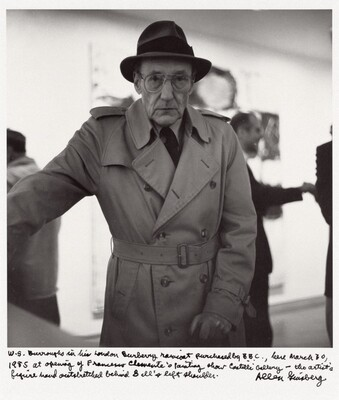 W.S. Burroughs in his London Burberry raincoat purchased by B.B.C., here March 30, 1985 at opening of Francesco Clemente's painting show Castelli Gallery — the artist's figure hand outstretched behind Bill's left shoulder.