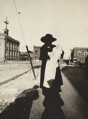 Untitled (Woman holding baby on street)