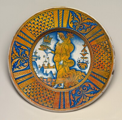 Large dish with segmental border of plant sprays and scale pattern; in the center, an emblematic female figure holding a crowned toad and cornucopia
