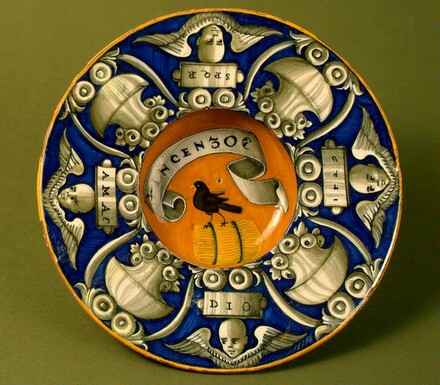 Broad-rimmed bowl with border of urns and cherubs' heads; in the center, device of a bird standing on a bundle with the inscription VINCENZO