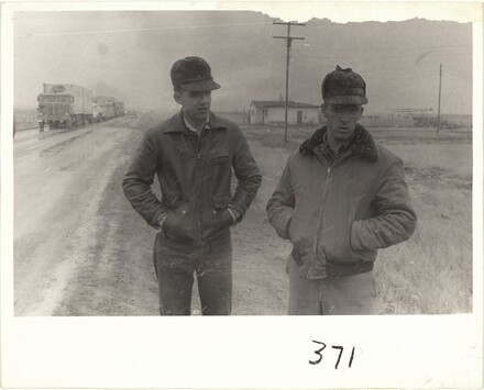 Two men standing by side of road in snow--U.S. 66 between Winslow and Flagstaff, Arizona