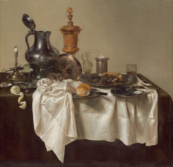 """A jumble of pewter plates and a pitcher, glass goblets, a gold chalice, a brass candlestick, and other vessels along with lemons, olives, and the remains of a mince pie are arranged on a creamy white tablecloth bunched on a dark evergreen tabletop in this square still life painting. The scene is painted almost entirely in shades of cool grays, gold, brown, and white against a deep beige background. The objects span width of the canvas across its center. At the left edge of the painting, a vibrant yellow lemon has been cut so its rind curls in a spiral that hangs over the front edge of the table. Behind the lemon, a scissor-like candle snuffer is propped against the wide ledge of the tall brass candlestick, its white candle nearly burned down. A few glistening olives sit in a small pewter plate and one olive sits on the tabletop near the lemon and candlestick. A glass goblet with a wide stem with textured knubs rests upended on an elaborately chased, gold, footed vessel that has been tipped over so its wide shallow bowl faces away from us. The tall pewter pitcher behind this is dented on its rounded body. The lidded gold chalice next to the jug is the tallest object in the painting. Next to the chalice, along the right half of the painting, is a glass oil cruet with a long, curving spout, a tall, cylindrical vessel holding a small pile of salt, and a straight-sided, low glass holding beer. In front of these objects, an untouched bread roll and knife sit on a pewter plate at the center of the composition, tucked partially under the rumpled white tablecloth. The remains of the mince pie with its pastry crust on a large pewter plate sits behind another plate holding a broken goblet and a piece of black and white paper rolled into a cone. A few empty oyster shells sit on the table to the left and right, near the lemons and mince pie. The artist signed and dated the painting along the edge of the white cloth near the lower right corner: """"HEDA 1635."""""""