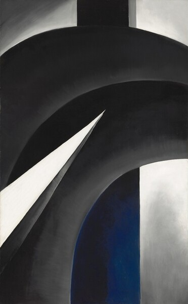 This vertical, abstract painting is made up of overlapping, intersecting geometric forms in shades of gray, cobalt blue, white, and black. The largest form is made up of a pair of black bands, running side by side, that extend up from the lower left corner to curve to the right off the edge of the composition beneath the upper right corner. The bands are shaded with pale gray along the bottom edges. In front of that curving black form, a vivid white, narrow triangle like a blade cuts into the composition from near the lower left corner, and it stretches halfway across the painting at an upward angle. The bottom edge of the triangle is painted nickel gray, suggesting that it has another facet in a three-dimensional form. A vertical shaft running behind the curving form is black at the top and cobalt blue where it is nestled under the curving form. Where the shaft is black along the top, the right edge is painted with a narrow strip of smoke gray. The area in the upper left corner and along the right edge of the canvas reads as a background behind the other forms. The background lightens from steely gray at the corners to brighter white near the center.