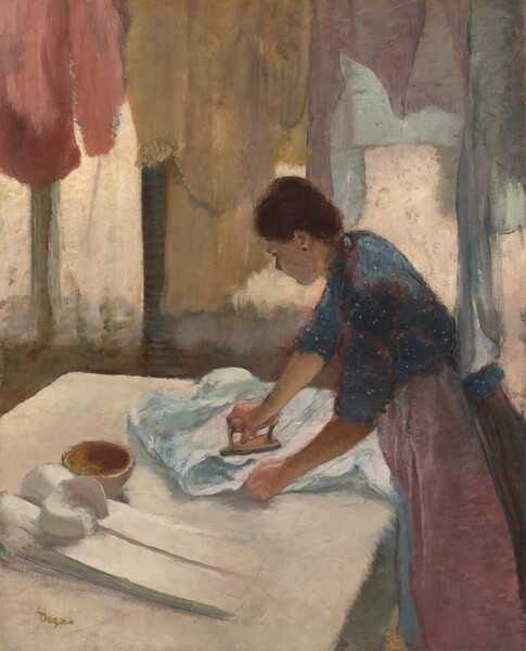 """A woman with peachy skin stands facing our left in profile ironing a pale blue shirt on a white surface, possibly a table, with a line of pastel-colored shirts hanging in front of curtained windows on the far opposite us in this vertical painting. We seem to look slightly down onto the woman's shoulders and onto the surface of the table, as if from slightly above. The white tabletop takes up most of the bottom half of the composition, and, seen from the knees up, the woman leans in from the lower right corner. The woman's chestnut brown hair is pulled up into a bun and she wears a dark earring in her left ear. Her denim blue dress is speckled with white dots and highlighted with strokes of blush pink. Her sleeves are rolled up to the elbow and a dusty rose apron covers her brown skirt. She presses down on the iron with her right hand, farther from us, and uses her left hand to straighten the fabric of the shirt collar. The iron has a thick handle and a flat, narrow, triangular surface used to press out wrinkles. A small, empty bronze colored bowl and crisply starched and folded porcelain-white shirt lie on the table to her left, closer to us. A row of hanging garments in pale crepe pink, flaxen gold, teal, and lavender soften the light coming into the room from three vertical windows, which are covered with sheer ivory white curtains. The artist's feathery brushstrokes give the painting a hazy quality. The artist signed the work with olive green letters near the lower left corner: """"Degas."""""""