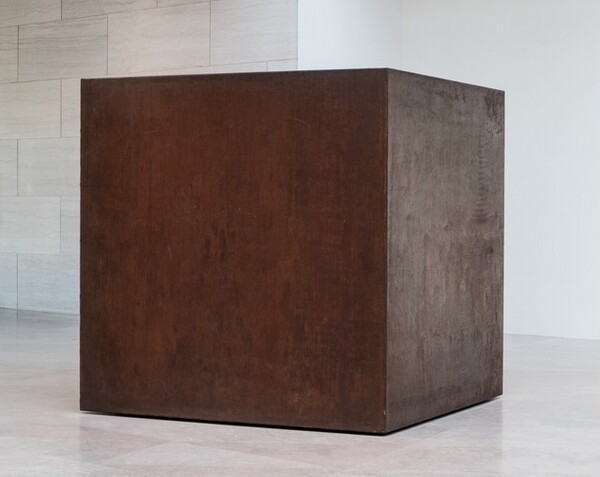 A rust-brown steel cube sits directly on a stone floor in a gallery. This photograph shows the cube from near one of the corners so two sides are visible. The surface of the steel is mottled and faintly streaked. The bottom edge of the cube seems to float slightly, creating the impression that hovers just above the floor. The room around the cube has flat marble panels to the left and a white wall to the right.