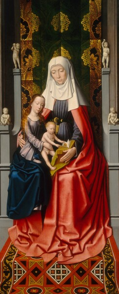 Two women and a baby, all with pale skin, sit together on a gray, stone throne with patterned fabric hanging behind them and a patterned rug below in this narrow, vertical painting. The woman sitting on the throne, Saint Anne, is the largest. A second woman, Mary, is smaller in scale, and she sits on Saint Anne's lap and, in turn, holds a nude baby boy on her lap. Both women have light brown eyes under faint, arched brows, smooth skin, long straight noses, and their shell-pink lips are closed. Saint Anne sits with her body facing us and she looks down with her head slightly tilted to our left. Her white head covering drapes over her shoulders and hangs down from her chin to cover her neck. She wears a marine blue dress cinched at her waist with a black and gold belt, and a crimson red robe that falls to and puddles around her feet. Her right arm, on our left, wraps around and holds Mary's hip, and she supports a book with gold edged pages with her other hand. Mary sits on Saint Anne's right thigh, on our left, and leans toward the baby, who sits on her left knee, on our right. Her long, wavy, golden brown hair falls over her shoulders and she wears a cobalt blue robe over a lilac purple dress. The baby has short, curly blond hair and reaches to turn the pages of the book. He has rounded cheeks and a pudgy torso. The stone throne is ornamented on the arms and at the top corners with ivory-colored, nude children, presumably to resemble putti carved out of stone. The cloth hanging behind Saint Anne is decorated with glimmering gold, ornamental leaf designs against a pine-green background. The rug beneath her feet is a geometric pattern of red, tan, black, and white.