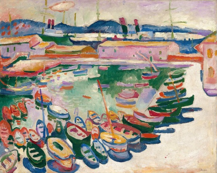 """We look across a sandy colored beach or walkway that stretches away from us to our right and then turns ninety degrees to our left in the distance, to enclose a teal-colored body of water filled with rows of small rowboats in this nearly square, stylized landscape painting. The scene is loosely painted with vibrant colors, in jewel-toned topaz and royal blues, emerald and mint greens, pale orchid purple, golden yellow, cream-white, and crimson red. The boats grouped along the beach close to us are lined up in a row along the beach to our right, punctuated by a few vertical masts. The beach across from us in the distance is lined with a cotton candy-pink, pale lavender purple, sage green, and pumpkin-orange warehouses in front of a line of cobalt-blue mountains along the horizon, which comes nearly to the top edge of the canvas. The sky is pastel purple, green, yellow, and peach above. The artist signed the work in dark paint in the lower right corner: """"Braque."""""""