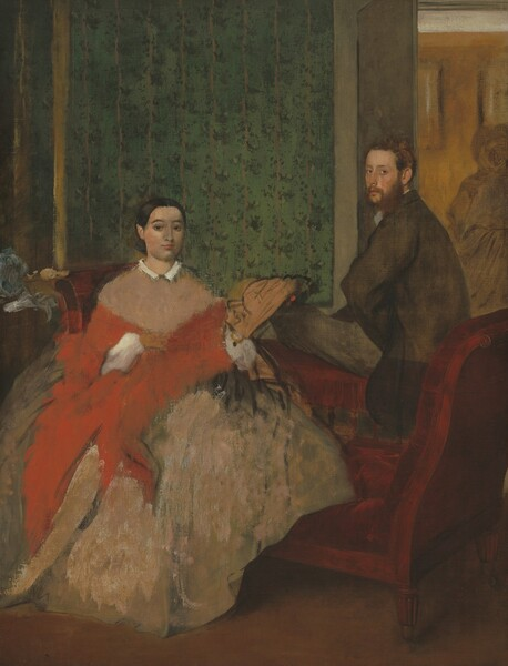 A man and woman sit on opposite sides of a burgundy-red, low-backed sofa in a room wallpapered with a striped floral pattern against a moss-green background in this vertical painting. To our left, the woman sits with her body facing us, and she looks at us with dark eyes under dark, arched brows. She has an oval face, a straight nose, and her coral-pink lips are closed. The skin on her face is pale peach to our left and almost sage-green to our right, where the paint has been lightly scraped away. The woman's dark brown hair is parted down the middle, and smoothed and pulled back to the base of her head. Her pinkish-tan dress has a narrow white collar and a full, billowing skirt. A loosely painted, crimson-red shawl wraps around her torso and is pulled over white, puffy sleeves. Also loosely painted, a shell-shaped, tan object to our right could be a fan held in her left hand. To our right, the man sits on the low back of the chaise-longue, his left knee bent so that thigh, closer to us, rests along the back of the sofa. He has pale peach skin and turns his face to look at us with teal-blue eyes from the corners of his eyes. He has a rounded nose, and his full, pink lips are closed. He has an auburn-brown beard and his short hair seems tousled. He wears a brown coat and charcoal-gray slacks. He rests the hand closer to us against his hip so his elbow juts toward us. To either side of the people and nearly spanning the width of the painting, the arms of the chaise curve upward to about the height of the woman's shoulders. A loosely painted, ball-like form next to the left arm of the chaise, and could be a hat or other object on a side table. The wall behind the people extends from the left edge of the painting to just behind the man, and is patterned with evergreen-colored dots reminiscent of floral patterns along vertical beige-colored stripes, all against the moss-green background. A golden yellow, vertical line near the left edge of the painting may be the frame o