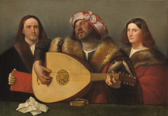Seen from the waist up across a forest-green ledge or tabletop, a bearded man with a ruddy complexion strums a six-stringed lute between two, light-skinned people in this horizontal painting. The green ledge runs close to the bottom edge of the canvas and the people nearly fill the composition. The musician's body faces us but he looks up and off to our left with gray eyes, possibly under raised, arched brows, with lips parted. His long brown hair is covered with a ruby-red hat wrapped with a pale, petal-pink band. The ribbon meets in a bow-like form near the front center, and tassels hang to each side. His voluminous coat has wide, tawny, orange-colored fur lapels and is lined with fur where it splits open over his shoulders. The garment below has dark sleeves. He lifts his right shoulder high over the lute as it rests on the tabletop, to play it with the neck to our right. The soundhole at the center is carved with rosette-like tracery. The man to our left has long, straight, dark brown hair and a cleft in his chin, which is darkened with a five o'clock shadow. He looks down and towards the musician with brown eyes over a long nose, and his lips are closed. He wears a black cloak with a fur collar over a white shirt, and holds a book with a ruby-red cover. To our right, a young person, possibly a man with delicate features, stands with his body angled toward the musician but turns his face to look at us with gray eyes. He has flushed cheeks, a long, straight nose, and a rounded chin. He has shoulder-length, wavy brown hair parted down the middle and wears a red cloak also with a fur lapel, over a cream-white undershirt. A crumpled white cloth and a small, oval-shaped box with its lid askew sits on the green surface near the lute. The background behind the trio is elephant gray.