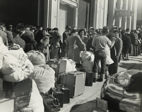 Residents of Japanese ancestry awaiting the bus at the Wartime Civil Control station, San Francisco, California