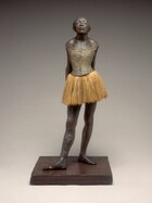 An adolescent ballerina stands before us with her hands clasped behind her lower back, her head tipped back, and her chin thrust forward. The skin of her face, arms, chest, and legs has been painted bronze-brown, and her body faces us in this photograph. The sleeveless putty-gray bodice of her costume fits tightly above a layered, fabric, pale, tea-brown tutu, and she wears ballet shoes. Her hair is pulled back but bangs sweep across her forehead, brushing her nearly closed, heavy eyelids. Her lips are slightly parted and light catches the broad planes of her cheekbones. Her shoulders are drawn back by her pose, holding her hands behind her with arms straight, and her hips jut slightly forward. She stands with her right foot extended in front of her, with both feet turned out, parallel to each other.