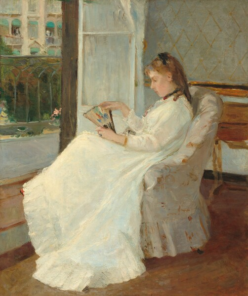 A young woman with pale peach skin and light brown hair sits in profile facing our left in an upholstered chair in this vertical painting. The chair and woman take up most of the composition so seems close to us. She wears a long-sleeved white dress that sweeps to the floor, with black ribbons around her neck and atop her shoulder-length ringlets. The dress has small ruffles at her throat and a deep flounce at the bottom. She gazes down at the partially open fan she holds on her lap. The fan is touched with spots of pumpkin orange, turquoise, plum, and royal blue on a beige background. Loose, swirling brushstrokes in golden tan and bright white against an ivory background suggests that the chair is upholstered with a floral-patterned fabric. A wooden desk or table is pushed against the wall behind the woman to our right and to our left, a white door, covered by a white curtain, opens onto a balcony with a wrought iron railing. Across the street, a couple of people lean out of open windows covered by teal awnings on a cream-colored building.