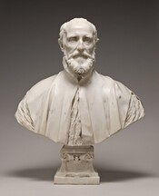 This white marble sculpture shows the head, shoulders, and upper chest of a balding, bearded man. He gazes straight ahead and seems to look at us in this photograph. Bushy eyebrows arch low over deeply set eyes, and his forehead hollows inward at his temples. He has high cheekbones and the skin of his cheeks draws slightly in. His thin lips are set in a straight line within a full beard. His high-necked robe falls slightly open over his chest and is cut away over the shoulders to show the crinkled fabric of the garment beneath. The bottom edge of the sculpture curves upwards in a very shallow U across the bottom, and is supported by a square pedestal foot decorated with scroll designs.