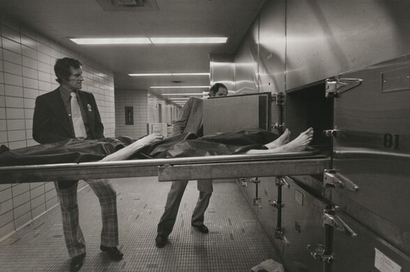 Homicide detectives produce fingerprints from a corpse in the city morgue, New York City