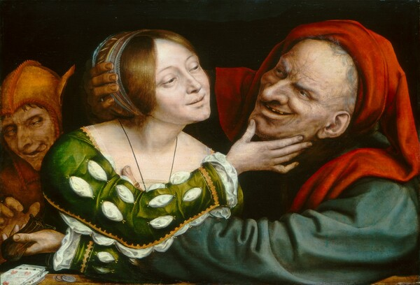 A woman with smooth, pale skin and an elderly man with exaggerated features embrace and gaze into each other's eyes while a person dressed in the orange costume of a fool lurks behind them to our left in this horizontal painting. All three people have white skin and are shown from the chest up behind a ledge or tabletop against a black background. The older man to our right wears a dark teal garment and a bright crimson head covering that drapes over both shoulders. Wrinkles and age spots cover his face, which is accentuated by a bulbous nose and a leering smile that exposes missing teeth. His arms reach out and encircle the woman to our left. Cradling the right side of her head with his right hand, his left arm reaches across to her upper body, his thumb visible at her breast. A blue and gold band holds the woman's auburn hair back. A white shift peeks through the slashed sleeves of her emerald green, gold-trimmed gown. She reaches toward the elderly man with her right arm, her hand tenderly holding his chin. Her left arm reaches across her body under his arm and she holds a leather pouch, probably containing coins, in that hand. A man wearing an orange cap with asses' ears, reaches for the pouch, eyes crossed and his tongue protruding from the side of his mouth. Playing cards and coins lie on a tabletop to our left.