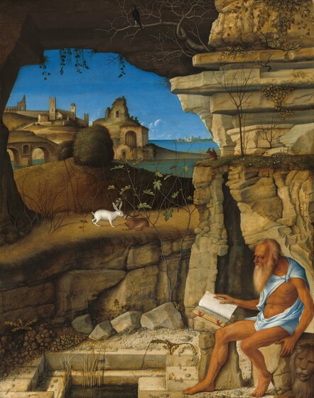 A bearded and balding man with sun-browned skin, dressed only in a strip of robin's egg-blue fabric around his shoulders and hips, sits reading a book on a rock in front of a craggy cave, set in a landscape with stone buildings and a body of water in this vertical painting. The man, Saint Jerome, faces our left in profile, his head bowed towards the open book propped on the rock next to him farther from us. His hair and beard are parchment-white, and he has a prominent brow ridge, a long, hooked nose, and sunken cheeks. His arms and legs are sinewy and his torso seems muscled. The blue cloth is knotted over his left shoulder and wrapped around his hips. A lion lays next to Saint Jerome's rock in the lower right corner, its face towards us with mouth slightly open. There is a rectangular pool lined with brick-like stones at Saint Jerome's feet, and the cave behind him has a jagged, narrow, vertical entrance with rocky outcroppings above and to our left, over the pool. A stone arch spans the top edge of the painting, enclosing the scene below. Other animals appear around Saint Jerome, including a lizard near the pool; two rabbits, white and brown, on a rocky protrusion across from Saint Jerome to our left; squirrel on the grassy top of the cave entrance; and a black bird in the barren branches of a tree growing from the rocks above the cave. Beyond a low hill of grass topped by a bush or tree, a cluster of golden-brown stone buildings, some in ruins, spread down a hillside to the water's edge. Across the water to our right, deep in the distance, white buildings line the horizon, which comes about two-thirds of the way up this painting. A few puffs of white clouds float along the waterline against a vivd, azure-blue sky above, which is enclosed by the ragged, stone arch over Saint Jerome.