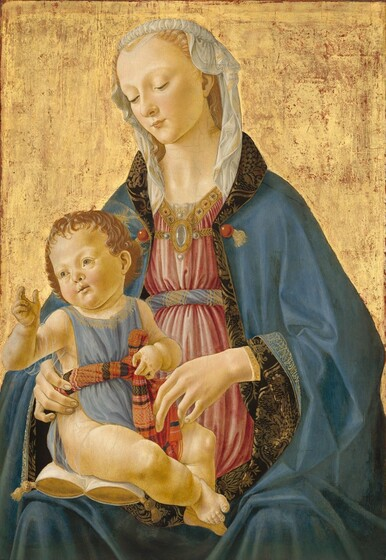 Against a gold background, a blond woman is shown from the lap up, facing us as she holds and looks down at a plump baby sitting on a gold and white pillow on her right thigh, to our left, in this vertical painting. Both people have pale, peachy skin and faint halos encircle both of their heads. The fair-haired child sits with his body angled towards his mother but he turns to look off to our left, pale green eyes bright. He holds his right hand, on our left, up with his thumb and first two fingers raised. He has rounded cheeks, a delicate nose and lips, and chubby legs. He wears a light blue smock edged in gold, with a gold filigree at the collar. It is belted with a twist of fabric patterned in bands of red, black, and gold. Under the smock he wears a half-sleeved, transparent undershirt. The woman steadies the baby with her long, delicate hands. She wears a sky-blue robe edged with gold, Arabic-like script. The lining, in a black and brown floral pattern, is visible where the edges of her robe turn back over her wrists and around her neck. Belted across the chest in a twist of blue and gold fabric, her dusky pink dress is topped at the neck in a gold yoke set with red and blue gems, with a brooch of pearls and rock crystal. Her headdress is of translucently fine white cloth bordered with a gold stripe, rolled atop her head and falling loosely to her shoulders.