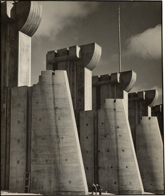 Four monumental concrete structures nearly fill the space of this vertical black and white photograph. The fortress-like architectural forms are arranged in a line so they move away from us at a diagonal to our right to create an almost abstract composition. Each structure seems to be made up of two parts: a form that tapers from a wide base to a narrow top seems to brace a taller form, which is topped with a semi-circular, crown-like crenellation. The top of the leftmost structure is cropped and its bracing foot reaches halfway across the composition. Two people stand at the base of that structure, barely coming a tenth of the way up the lower bracing structure. Deep shadows on our side of the structures contrast with the brighter areas highlighted by the sun. Two clouds float in the sky above. A tall pole supporting a wire nearly reaches the top edge of the photograph to our right.