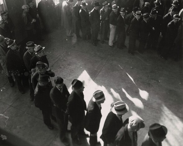 Line of men inside a division office of the State Employment Service office at San Francisco, California, waiting to register for unemployment benefits