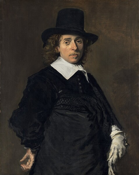 Seen from about the hips up, a man with peachy skin, wearing an ink-black hat and coat with a bright white collar, looks out at us against a brownish, olive-green background in this vertical portrait painting. He stands with his body angled to our right and his face turned to look at us with dark gray eyes. His slim face is framed in long, brown curls under his tall, brimmed hat, which is cocked a little to our right, away from us. He has a straight, prominent nose, lightly flushed cheeks, and a wispy, light brown mustache above a stamp of a beard beneath his lower lip. His neck is encased in a broad, starched, white linen collar, its wings laying along his collarbones. His velvety black coat has a row of tightly spaced buttons down the front and sleeves of elephantine puffiness. A cummerbund or sash wraps around his waist and hips. He rests his right hand, on our left, against his hip near his lower back, palm facing out. He wears a light, dove-gray glove on his opposite hand, and holds a second glove in that same hand. The portrait is painted loosely, with broader brushstrokes in some areas, such as the hand at his hip and in the folds of the black garments.