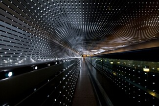 An installation made up of dozens of rows of bright white lights nestled between silver-gray slats in a long tunnel fills this horizontal photograph. The alternating lines of lights and slats move away from us to almost come together around a narrow, capsule-shaped area of golden yellow light at the far end of a tunnel, at the center of the photograph. The ceiling runs straight across the top of the photograph and curves down to meet the wall to our left. The curve continues to make a C-shape before extending straight down the remaining height of the wall, turning the profile of the open space into a backwards-facing P. Some of the lights are bright, some fading, and some are off to create a loose pattern of dark squares floating in a field of light. The lights seem brighter at the far end of the tunnel. The overall impact of the view is a starburst radiating in diagonal lines, coming from a point at the center of the photograph.