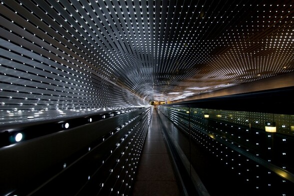 We look through a tunnel lined with dozens of strings of bright white lights nestled in silver-gray slats that extend away from us in this horizontal photograph. The alternating lines of lights and slats move away from us to almost come together around a narrow, capsule-shaped area of golden yellow light at the far end of a tunnel, at the center of the photograph. The ceiling runs straight across the top of the photograph and curves down to meet the wall to our left. The curve continues to make a C-shape before extending straight down the remaining height of the wall, turning the profile of the open space into a backwards-facing P. Some of the lights are bright, some fading, and some are off to create a loose pattern of dark squares floating in a field of light. The lights seem brighter at the far end of the tunnel. The overall impact of the view is a starburst radiating in diagonal lines, coming from a point at the center of the photograph.