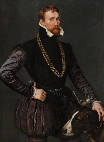 "Shown from the thighs up against a dark background, a man with light skin, wearing a black satin jerkin with puffed breeches, stands with his hand on the neck of a dog by his side, filling this vertical portrait painting. The man stands with his body angled to our right but looks at or toward us from the corners of his dark eyes. His brows are subtly raised and his cheeks are slightly sunken under high cheekbones. His red hair is cut short and his red mustache and beard are trimmed. The high collar of his black jacket is lined with a white ruffle along his chin line. Light from our left glints off the long sleeves of his tight-fitting jacket, creating the impression that it is made of heavy silk. Two thick gold chains hang down his chest, and a sword hangs from a belt around his waist, the hilt on the hip farther from us. His pants puff out and gather on the mid-thigh, presumably over stockings. He hooks the thumb of his right hand, on our left, around his hip and he rests his opposite hand on the neck of the dog standing by his left side, to our right. The dark brown dog has a white stripe down its nose. It faces our left in profile but its brown eyes look toward us. On his collar, ornate metal bosses alternate with low spikes, set in a wide black band. A ring hangs from the front of the collar. Barely legible, the painting is signed and dated in the upper left corner with dark paint: ""Antonius mor pingebat a. 1569."""