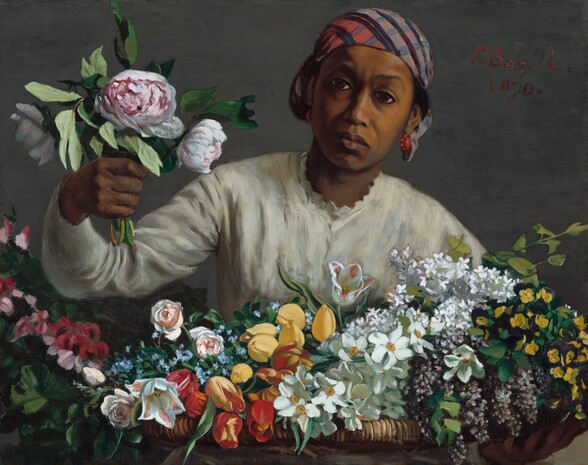 """Holding a bunch of peonies in one hand, a woman with brown skin leans forwards towards us from behind a large basket holding dozens of flowers, in this horizontal painting. The basket holding the flowers spans the width of the canvas, and the woman is seen behind it from the chest up. She wears a cream-colored, long-sleeved blouse with scalloped trim around the high neck. She wears coral-colored earrings, and a plaid cloth in tones of coral, blue, pale purple, and black is tied tightly over her black hair, which is visible over her hears. Her brow is slightly furrowed and she looks at us with large, dark eyes. Her full mouth is closed, the corners faintly downturned. She reaches her right arm, on our left, toward us with a bouquet of three pink-and-white peonies and greenery. Her basket is filled with yellow and red tulips, pink roses, white and purple lilac, and other white, pink, yellow, and blue flowers, and it takes up the bottom third of the composition. The woman and basket are shown against a slate-gray background. The artist prominently signed and dated the work with red letters near the upper right corner, near the woman's head: """"F. Bazille. 1870."""""""