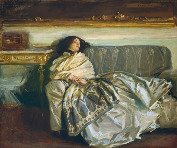 """Seeming close to us, a woman with pale white skin and dark brown hair reclines along a gray couch so her torso leans on the arm of the sofa to our left and her head rests on the backrest in this horizontal painting. Her torso is wrapped in a voluminous, ivory colored scarf or wrap. The bottom edge of the scarf is printed with an indigo pattern of ovals and vegetal forms, and it is gathered tightly at her throat. Her shimmering silver gray skirt is painted loosely with baby and denim blues, army and sage greens, white, and ivory strokes, and it drapes over the cushions and down the front of the couch. Her hands are clasped so her interwoven fingers rest at her navel. She looks down and off to our right. A table to our left is edged with gold. The wall behind her above the couch is painted with long streaks of eggshell white and pale turquoise. The gold frame of a dark painting hanging over the couch spans the width of the painting. Near the upper right corner of the canvas, the artist included a signature and as if he had signed the painting within this painting with loose, dark letters: """"John S. Sargent 1911."""""""
