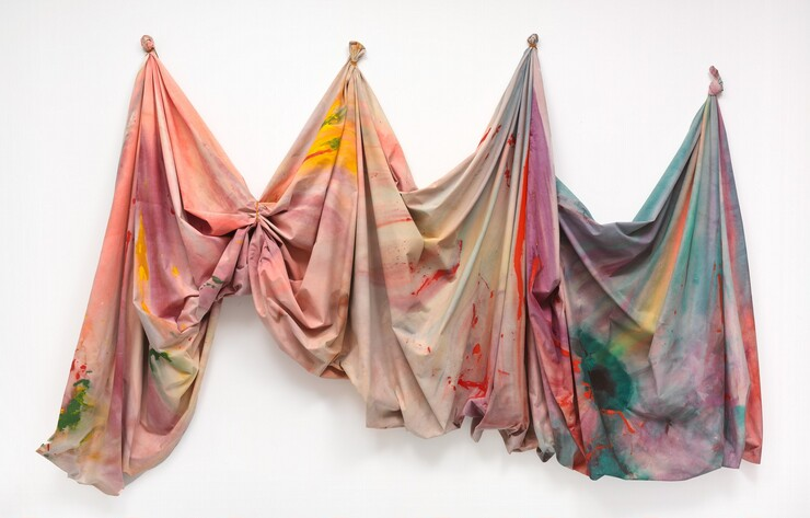 This painted canvas hangs on the wall loosely from four gathered peaks—one peak on each end to the left and right, and two peaks evenly spaced in between. The fabric is tightly wrapped with a leather cord into a fist-like form to create each peak, except for the right-most peak, where the fabric is knotted. The canvas is stained with large areas of soft color that largely meld together, with mostly pink, peach, and yellow to the left that transitions to violet, turquoise, and sky blue to the right. Hard-edged, vivid orange streaks break through the blues and greens to the right.