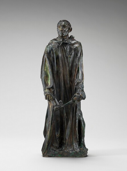 Cast in bronze, this sculpture shows a man with a gaunt face and wearing a robe that falls in long, vertical folds, holding a large, oversized skeleton key as he looks off to our left. In this photograph, the man's body faces us but he turns his head to our left, his chin sightly raised. He has close-cropped hair, sunken eyes, hollow cheeks, a wide, square chin, and his thin lips are downturned. The long-sleeved robe drops heavily to his feet. A hint of a raised, round halter like a yoke around his neck shows from under his robe near his left shoulder, on our right. He holds the key with arms straight down and in front of him, his knuckles standing out with tension. Most of the surface has a dark green patina except for a few lighter places, as on his sleeve to our left and in the thick drapes of his robe.