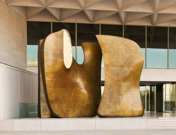 This horizontal color photograph shows a gleaming, abstract bronze sculpture that fills a two-story covered entryway. At least two tall, rounded, smooth forms sit side-by-side, almost as if they had been modeled using dough or clay. The form on our right curves slightly inwards up the left side and swells into a shallow hourglass-like form along the right side. The form on the left is shaped like a fat U with a deep, wide curve at the bottom. Most of the sculpture's surface is lightly mottled in a rich honey color, except at the top of the front face of the U's arm, which looks as if it were cut vertically to expose an elongated oval shaped disk of highly polished, bright gold colored bronze. A third form appears only as a straight vertical element behind and to the left of the U-shaped piece. The building behind and over the sculpture has two rows of floor-to-ceiling windows, which reflect darkly in this photograph. The floor and ceiling above are smooth, buff-colored stone. Two rows of deep-set triangles recede into the ceiling.