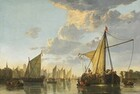 A fleet of ships gathers in a river lined by trees and buildings in this horizontal painting. The horizon is low, less than a quarter of the way up the composition, and the immense pale blue sky above is filled with clouds with golden tops above dove gray undersides. The river spans the width of the painting and is congested with boats and ships, many festooned with red, white, and blue flags and banners. The vessels are crowded with people, mostly men wearing hats and black or brown garments. A ship to our right seems the closest to us and is the largest in the composition. A rowboat has pulled up to the side of the ship, and is occupied by a seated man wearing crimson, a standing man wearing black, and another wearing brown, who pulls the rowboat closer to the ship. Amid the densely packed deck over the rowboat, a musician plays a drum while another drinks from a flagon. Ships with unfurled sails, rowboats, and ferries fill the river behind and around the large ship. Churches and buildings are clustered along the riverbank to the left and trees line the river to the right.
