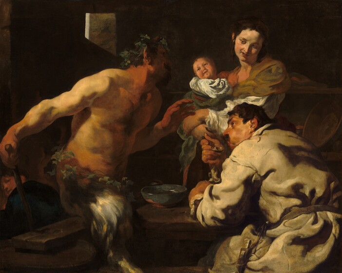 Shown from the about the thighs up, a man, a woman holding a swaddled baby, and a satyr, with a man's torso and goat's legs, sit and stand around a table in a deeply shadowed room, filling this horizontal painting. All the people have light skin and dark hair, and are lit dramatically from our left. To our left, the bare-chested satyr faces our right in profile as he leans toward the table, looking up at the woman. He wears a crown of leaves and has a dark goatee. Almost lost in shadow, a sable-brown horn juts up from his temple. Light falls across his bare shoulders, and his hands and neck are ruddy. Another ring of leaves encircles his waist over the silvery gray fur of his goat's legs. He holds his left hand, farther from us, in front of his chest with his open palm facing the couple to our right. His other hand rests at the top of a wooden staff behind his right hip, closer to us. The staff disappears behind the plank resting across at least one wooden barrel that presumably acts as the bench that he sits on or hovers slightly over. The second man sits at the table to our right, his back mostly to us as he looks over his left shoulder, up toward the satyr with his face in profile. One brow seems cocked over the dark eye we can see, and he has a prominent nose and a mustache. He wears a loose-fitting, long-sleeved, parchment-white garment tied around the waist. He blows across a soup spoon held to his lips, his cheeks puffed. He leans on his other arm, which rests on the tabletop near an ocean-blue bowl. Across the table, behind the seated man, a woman looks back at the satyr from the corners of her eyes, her coral-red lips curled up in a smile. Her body faces our left and she tilts her head to her left, our right, as she turns her face down toward that shoulder. Her dark brown hair is pulled up and back, and she wears an olive-green wrap over a white shirt. The baby she holds leans away from her chest to twist and look back at the satyr as well. A few details ev