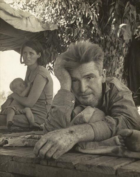 In this black and white, vertical photograph, a man, woman, and baby, all with pale skin, rest on blankets, or perhaps rugs, spread over a roughly built wooden platform under a leafy tree. Closest to us, the man takes up most of the right half of the composition. He lies on his stomach with his left arm, on our right, stretched out in front. His hand is close to the photographer so is slightly out of focus, and he cups his forehead with his opposite hand. The wooden platform on which he lies runs close to the bottom edge of the image. His light hair stands straight up from his head and he is cleanshaven. He wears a long-sleeved, button down shirt and looks off to our left and a little above us from under raised eyebrows and a creased brow. To our left, a woman sits beyond the man with her body angled to our left. Her chin-length dark hair is tucked behind her ears and her dress is worn with the seams tattered and gaping at the waist. She hunches slightly over the child she holds and looks up and to our left, her mouth open and her eyebrows knit. She seems to breastfeed her young, barefoot child who clutches her dress. The baby looks from the corners of wide eyes towards us. After seeing these three people, the toes and the ball of a person's foot, mostly cropped from the image, becomes noticeable next to the man, along the right edge of the photograph. A piece of cloth is tied into the branches above and over the woman to create a makeshift tent against the bright glare of the sun.
