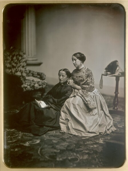Two light-skinned women wearing full, floor-length dresses sit angled to our left at the center of this vertical black and white photograph. The woman to our left sits on a patterned carpet wearing a black dress and holding an unfolded piece of paper in her lap. The woman to our right is wrapped in a flowery shawl worn over a lighter colored dress, and she leans against the shoulder of the woman to our left. Both look into the distance to our left. There is a chair upholstered possibly with a floral-patterned fabric in the background to our left and a side table holding a bonnet, the ribbons falling over the edge, to our right.