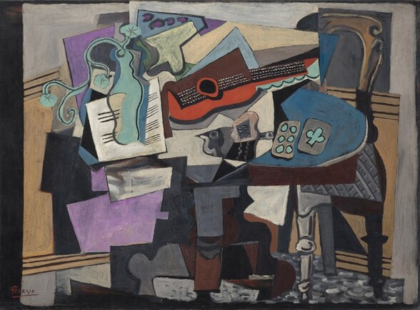"""A jumble of abstracted objects are gathered on a tabletop in this horizontal still life painting. The objects are made up of areas of mostly flat color and many are outlined in black, creating the impression that the some shapes are two-dimensional and assembled almost like a collage. The brown table has an oval top and a curving pedestal foot. At the center of the jumble on the tabletop, a guitar lies on its side with the neck facing us and reaching to our right. Beneath the black fretboard and neck, the curving form of the guitar is painted tomato red. The upper half is represented by a squared off brown form. The guitar seems to rest atop or in front of an array of stacked shapes, almost like splayed pieces of paper, in off white, lavender, and pale blue. A curving form painted in turquoise to our left seems to be a vase holding a spray of three flowers. The vase is shown against a white square painted with horizontal black lines, like sheet music. A dark gray form at the middle of the table, beneath the guitar, could be the silhouette of a bird facing our left. Just to the right of the bird, a pair of playing cards lie on a blue area. Painted in turquoise against gray, one card has six dots and the other one club. A chair with a curved, arching top and an elephant gray, basket-weave patterned upholstered seat is pulled up to the table to our right. The front left leg is light gray with turns near the foot and halfway up the leg; the right leg is painted black, as if in shadow. Panels of pale tan suggest wainscotting behind the table beneath a pale gray wall across the background. The overall impression of the painting is fragmented as even single objects seem to be broken up into planes and areas of color. The artist signed and underlined his name with red paint in the lower left corner: """"Picasso."""""""