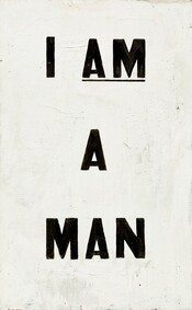 "The words ""I AM A MAN"" are painted in all capital, bold black letters against a white ground in this vertical painting. The words are spaced so they take up most of the composition, with ""I AM"" on the top line, ""A"" at the center of the composition, and ""A MAN"" at the bottom. ""AM"" is underlined. The white paint is thickly applied and brushstrokes, drips, and cracks are visible on the surface. A sliver of raw, off-white canvas is visible at the top right corner."