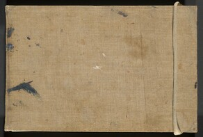 This tan-colored, fabric-covered sketchbook cover is marked with a few smudges of dark gray and white paint. The binding is to the left in this photograph. The cover is wide and has a cream-colored rope wrapped around the narrower end to our right. The weave of the fabric is visible. A few swipes of gray paint are spaced along the binding, to our left, and there are tiny touches of white, lavender purple, and brick red marking the cover.